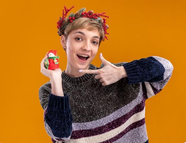 Beeindrucktes junges hübsches mädchen, das weihnachtskopfkranz hält und auf kleine weihnachtsschneemannstatue zeigt, die kamera lokalisiert auf orange hintergrund betrachtet