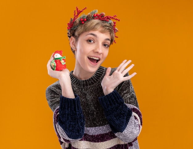 Beeindrucktes junges hübsches mädchen, das weihnachtskopfkranz trägt, der kleine weihnachtsschneemannstatue hält, die kamera zeigt, die leere hand lokalisiert auf orange hintergrund zeigt