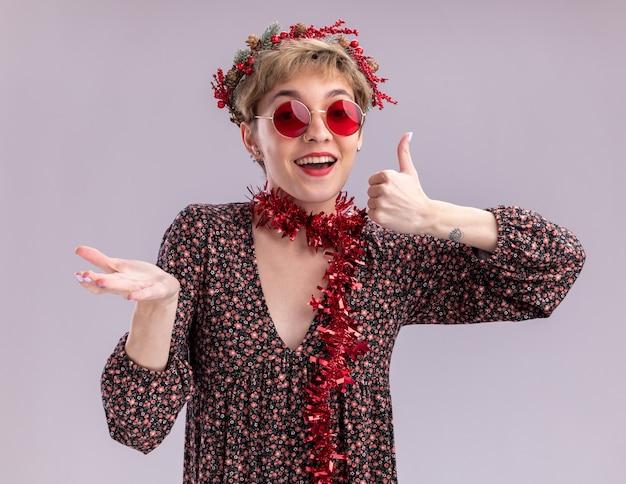 Beeindrucktes junges hübsches mädchen, das weihnachtskopfkranz und lametta-girlande um den hals mit den gläsern trägt, die kamera betrachten, die leere hand und daumen oben auf weißem hintergrund zeigt
