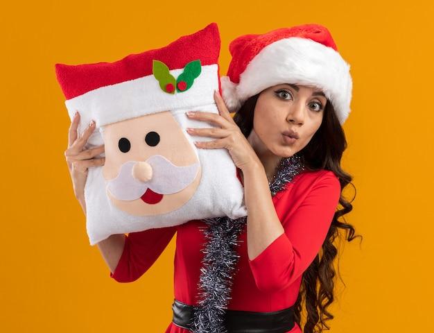 Beeindrucktes junges hübsches mädchen mit weihnachtsmütze und lametta-girlande um den hals, das ein weihnachtsmann-kissen hält und von hinten auf die kamera schaut und die lippen einzeln auf oranger wand schürzt Kostenlose Fotos
