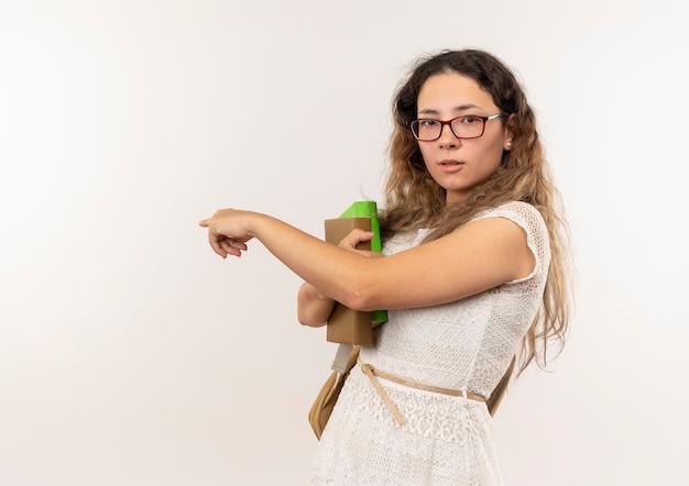 Beeindrucktes junges hübsches schulmädchen, das brille und rückentasche hält bücher hält und hinter isoliert zeigt
