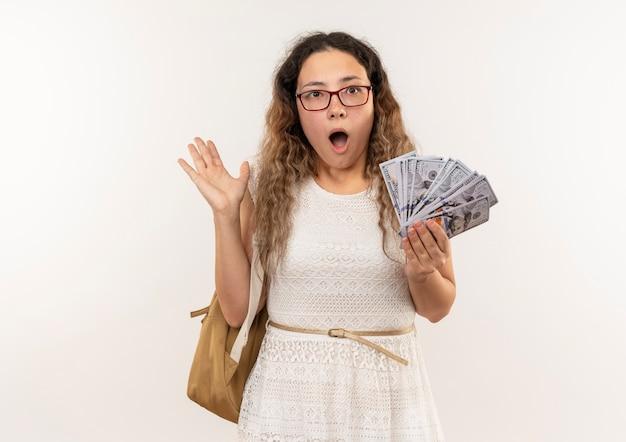 Beeindrucktes junges hübsches schulmädchen, das brille und rückentasche hält, die geld hält und leere hand lokalisiert auf weiß zeigt