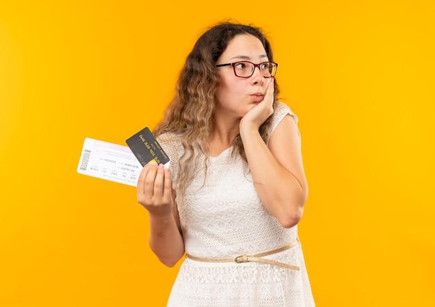 Beeindrucktes junges hübsches schulmädchen, das brille und rückentasche hält, die ticket und kreditkarte hält, die hand auf gesicht setzt, das seite lokal auf gelb betrachtet