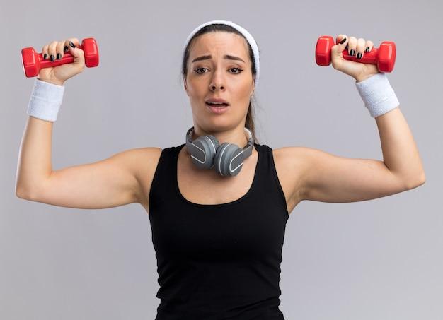Beeindrucktes junges hübsches sportliches mädchen mit stirnband und armbändern, das hanteln mit kopfhörern um den hals hebt, isoliert auf weißer wand