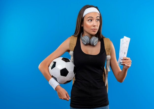 Beeindrucktes junges hübsches sportliches mädchen mit stirnband und armband und rückentasche mit kopfhörern am hals, das flugtickets mit fußball isoliert auf blauer wand mit kopierraum hält