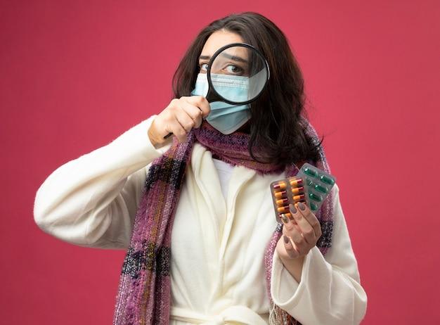Beeindrucktes junges kaukasisches krankes mädchen, das robe trägt, das packungen der medizinischen kapseln durch lupe hält, die auf purpurroter wand lokalisiert wird