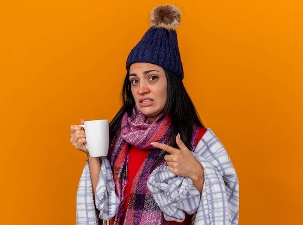 Beeindrucktes junges kaukasisches krankes mädchen, das wintermütze und schal trägt, die im karierten halten eingewickelt sind und auf tasse tee zeigen, der kamera lokalisiert auf orange hintergrund mit kopienraum betrachtet