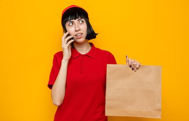 Beeindrucktes junges kaukasisches liefermädchen, das papierlebensmittelverpackungen hält und am telefon spricht