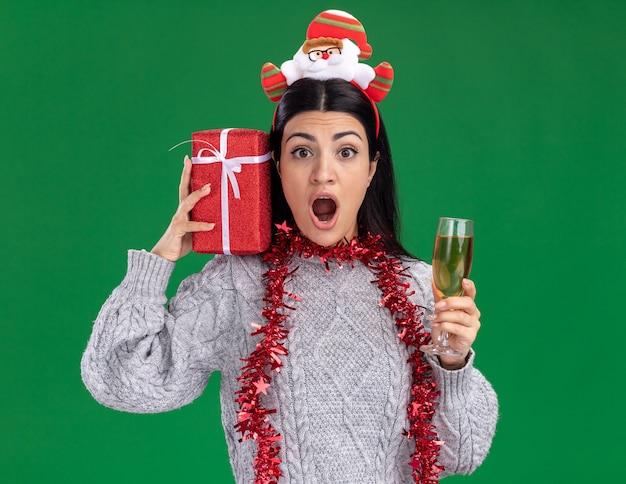 Beeindrucktes junges kaukasisches mädchen, das weihnachtsmann-stirnband und lametta-girlande um den hals hält, der geschenkpaket auf schulter und glas champagner betrachtet kamera lokalisiert auf grünem hintergrund hält