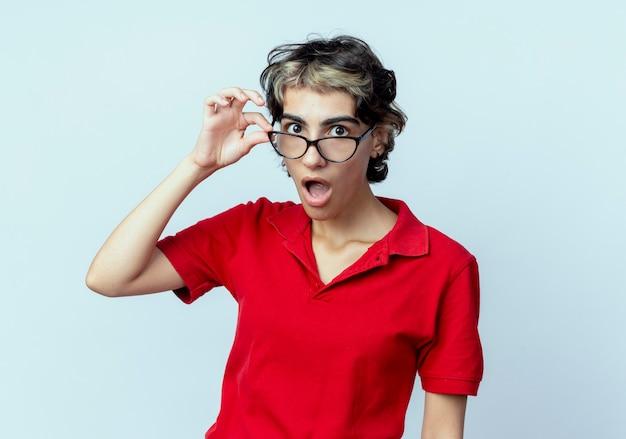 Beeindrucktes junges kaukasisches mädchen mit pixie-haarschnitt, das auf weißem hintergrund brille trägt und hält