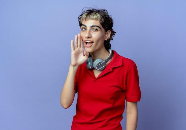 Beeindrucktes junges kaukasisches mädchen mit pixie-haarschnitt, das kopfhörer am hals trägt und hand nahe mund flüstert, der auf kamera lokalisiert auf lila hintergrund mit kopienraum flüstert