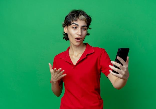 Beeindrucktes junges kaukasisches mädchen mit pixie-haarschnitt, der das handy hält und anschaut und die hand in der luft hält