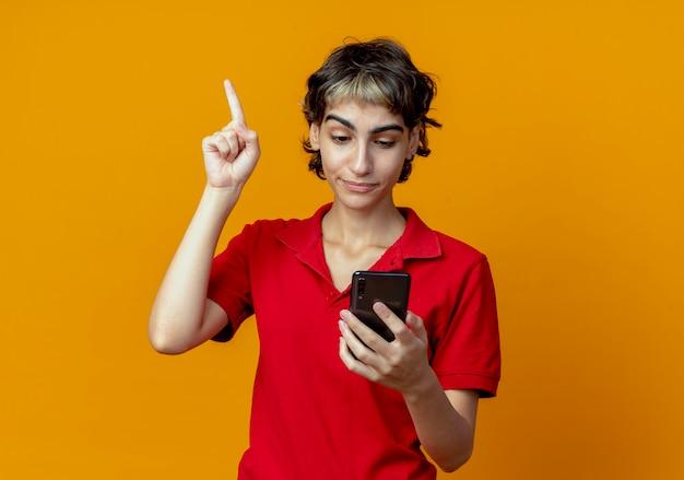 Beeindrucktes junges kaukasisches mädchen mit pixie-haarschnitt, der das handy mit erhobenem finger hält und betrachtet