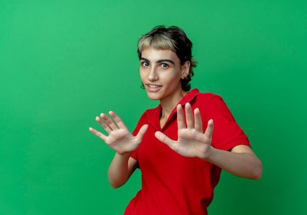 Beeindrucktes junges kaukasisches mädchen mit pixie-haarschnitt, der hände ausstreckt, die nicht isoliert auf grünem hintergrund mit kopienraum gestikulieren