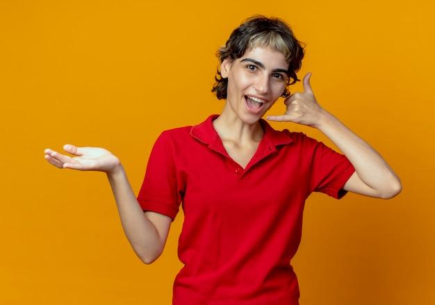 Beeindrucktes junges kaukasisches mädchen mit pixie-haarschnitt, der leere hand zeigt und anrufgeste lokalisiert auf orange hintergrund tut