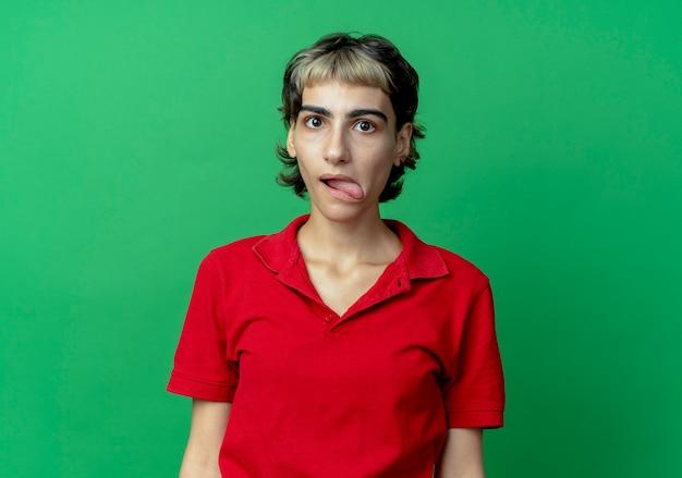 Beeindrucktes junges kaukasisches mädchen mit pixie-haarschnitt, der zunge zeigt kamera betrachtet auf grünem hintergrund mit kopienraum