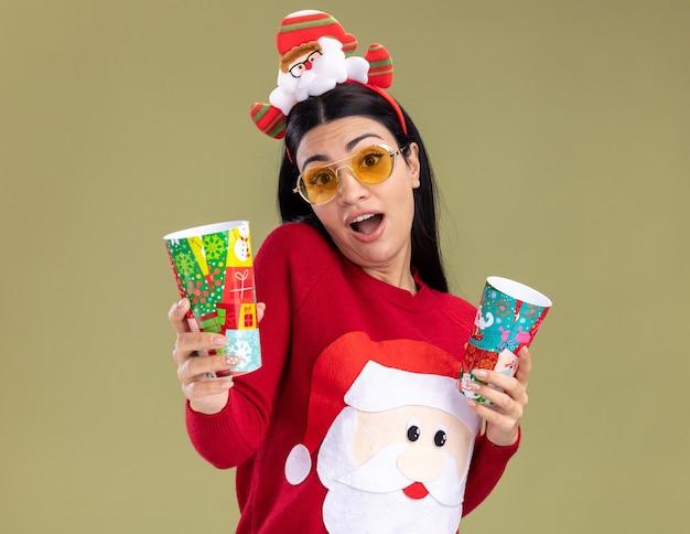 Beeindrucktes junges kaukasisches mädchen mit weihnachtsmann-stirnband und pullover mit brille, die weihnachtsbecher aus kunststoff hält, die sich einzeln auf olivgrüner wand ausstrecken?