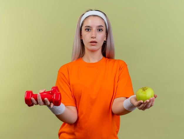 Beeindrucktes junges kaukasisches sportliches mädchen mit hosenträgern, das stirnband und armbänder trägt, hält hanteln und apfel