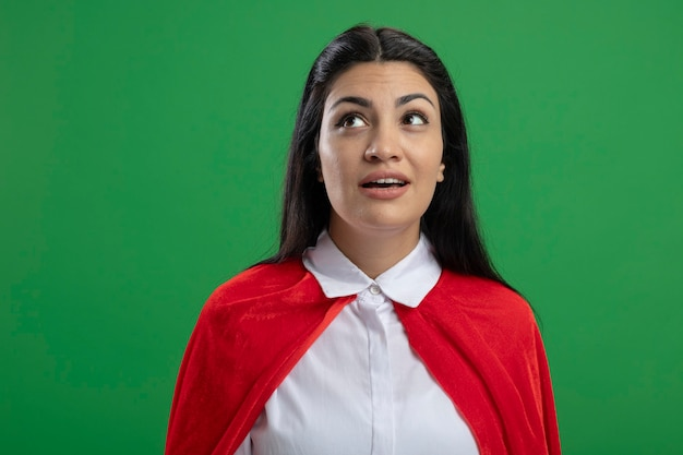Beeindrucktes junges kaukasisches superheldenmädchen, das rechts ohne irgendwelche zeichen steht, die lokal auf grünem hintergrund mit kopienraum suchen