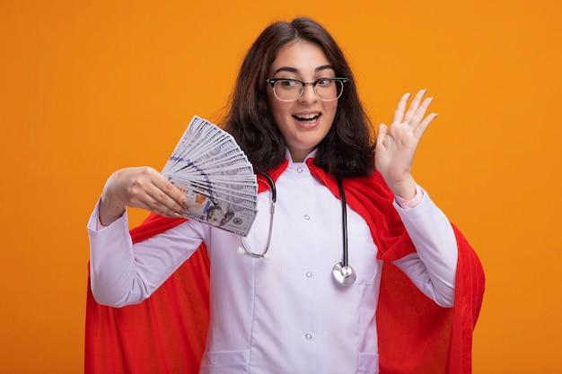 Beeindrucktes junges kaukasisches superheldenmädchen in arztuniform und stethoskop mit brille, das geld hält und ansieht, das leere hand isoliert an der wand zeigt