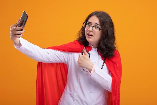 Beeindrucktes junges kaukasisches superheldenmädchen in rotem umhang in arztuniform und stethoskop mit brille, das selfie mit daumen nach oben zeigt