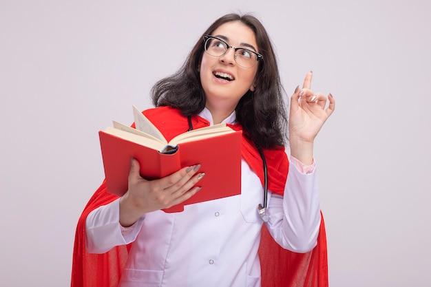 Beeindrucktes junges kaukasisches superheldenmädchen in rotem umhang in arztuniform und stethoskop mit brille, die nach oben schaut und zeigt