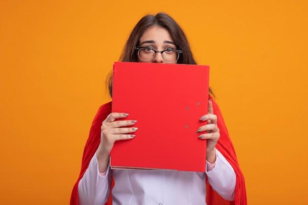 Beeindrucktes junges kaukasisches superheldenmädchen in rotem umhang in arztuniform und stethoskop