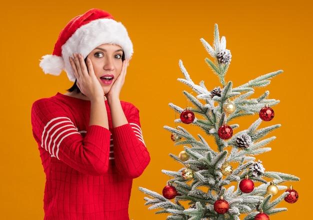 Beeindrucktes junges mädchen, das weihnachtsmütze trägt, der nahe verziertem weihnachtsbaum steht und hände auf gesicht hält, das kamera lokalisiert auf orange hintergrund betrachtet
