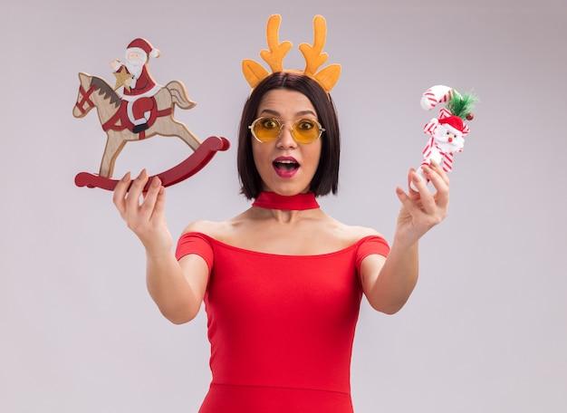 Beeindrucktes junges mädchen mit rentiergeweih-stirnband und brille, das den weihnachtsmann auf schaukelpferdfigur und zuckerstangenornament in richtung kamera ausstreckt, die auf die kamera isoliert auf weißem hintergrund blickt