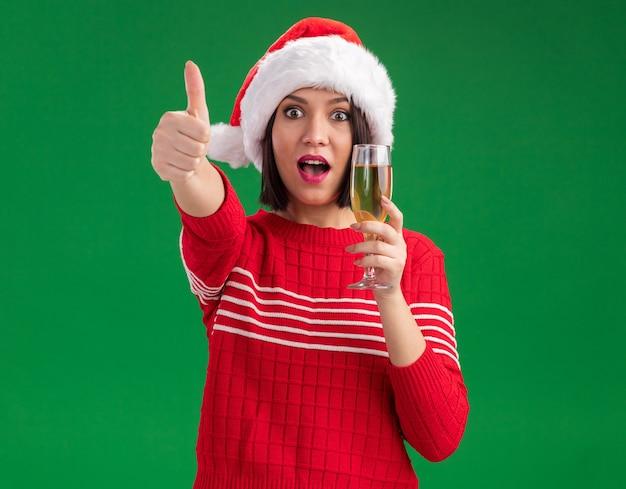 Beeindrucktes junges mädchen mit weihnachtsmütze, das ein glas champagner hält und in die kamera schaut, die den daumen einzeln auf grünem hintergrund zeigt