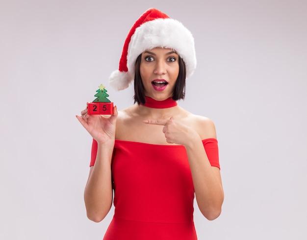 Beeindrucktes junges mädchen mit weihnachtsmütze mit weihnachtsbaumspielzeug mit datum, das auf die kamera zeigt, die auf weißem hintergrund mit kopienraum isoliert ist