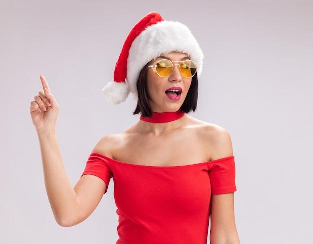 Beeindrucktes junges mädchen mit weihnachtsmütze und brille, das auf die seite schaut, die nach oben zeigt, isoliert auf weißem hintergrund