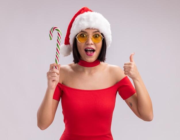 Beeindrucktes junges mädchen mit weihnachtsmütze und brille, das eine weihnachtszuckerstange hält und in die kamera schaut, die den daumen einzeln auf weißem hintergrund zeigt