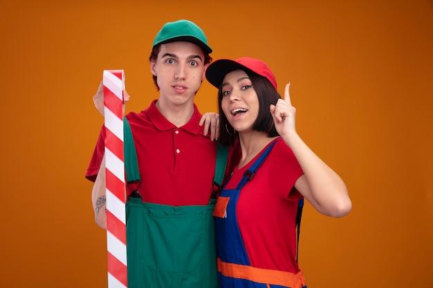 Beeindrucktes junges paar in bauarbeiteruniform und mützenmann, der sicherheitsbandmädchen hält, das hand auf jungs schulter hält, die nach oben zeigt