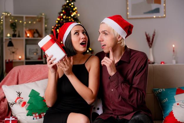 Beeindrucktes junges paar zu hause zur weihnachtszeit mit weihnachtsmütze auf sofa im wohnzimmer sitzend