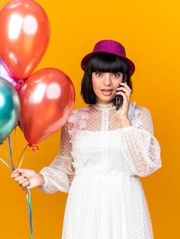 Beeindrucktes junges partymädchen mit partyhut, das luftballons hält und am telefon spricht, isoliert auf oranger wand