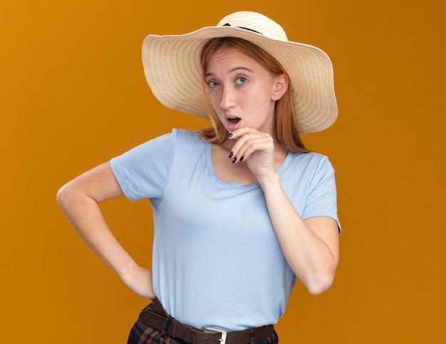 Beeindrucktes junges rothaariges ingwermädchen mit sommersprossen, die strandhut tragen kinn halten und kamera auf orange betrachten