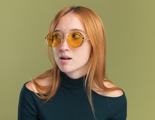 Beeindrucktes junges rothaariges ingwermädchen mit sommersprossen in sonnenbrille, das auf der seite isoliert auf olivgrüner wand mit kopierraum schaut