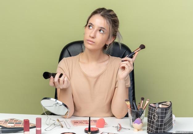 Beeindrucktes junges, schönes mädchen, das am schreibtisch mit make-up-tools sitzt und make-up-pinsel auf olivgrüner wand hält?