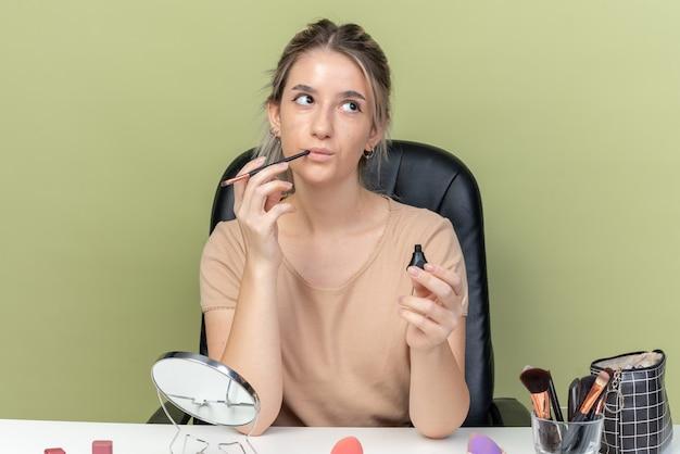 Beeindrucktes junges schönes mädchen, das am tisch mit make-up-tools sitzt und mascara isoliert auf olivgrüner wand hält