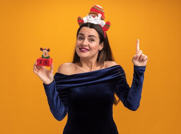 Beeindrucktes junges schönes mädchen, das blaues kleid und weihnachtshaarbügel hält, der spielzeugpunkte an oben lokalisiert auf orangefarbenem hintergrund hält