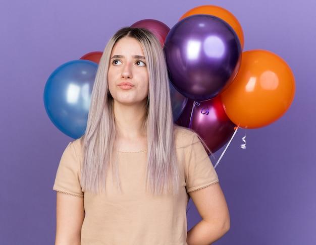 Beeindrucktes junges schönes mädchen, das vor ballons steht, isoliert auf blauer wand