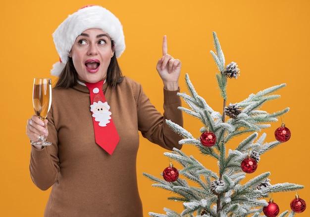Beeindrucktes junges schönes mädchen, das weihnachtsmütze mit krawatte trägt, die nahe weihnachtsbaum hält, der glas champagnerpunkte an oben lokalisiert auf orangefarbenem hintergrund hält