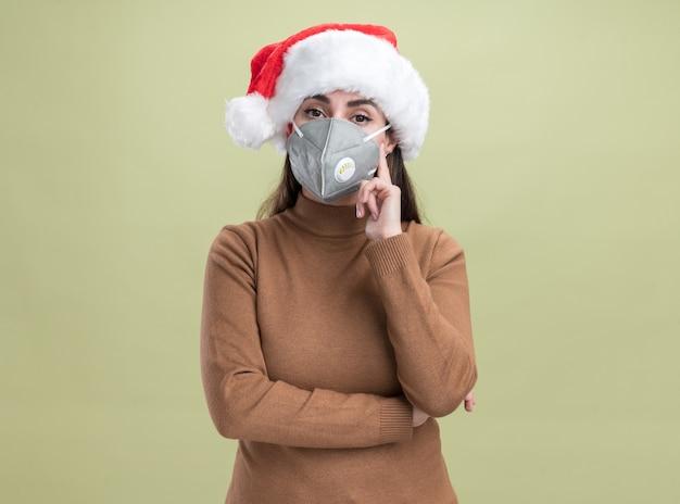 Beeindrucktes junges schönes mädchen, das weihnachtsmütze mit medizinischer maske lokalisiert auf olivgrünem hintergrund trägt