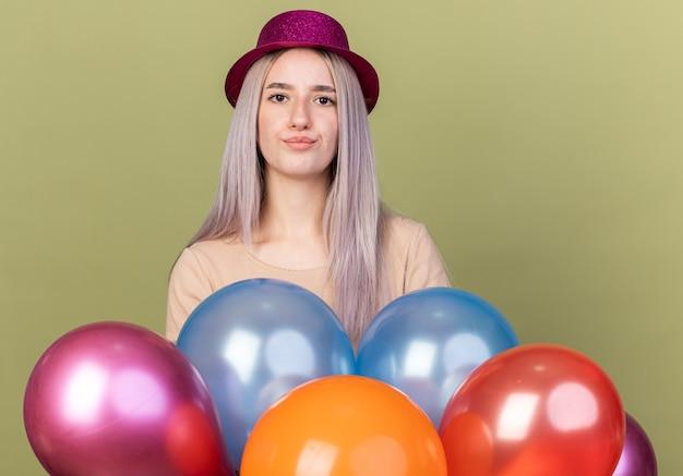 Beeindrucktes junges schönes mädchen mit partyhut, das hinter luftballons steht