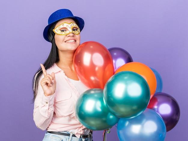 Beeindrucktes junges schönes mädchen mit partyhut und maskerade-augenmaske mit ballons zeigt nach oben isoliert auf blauer wand