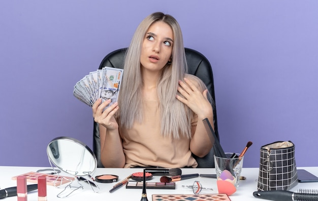 Beeindrucktes junges schönes mädchen sitzt am tisch mit make-up-tools, die bargeld isoliert auf blauer wand halten