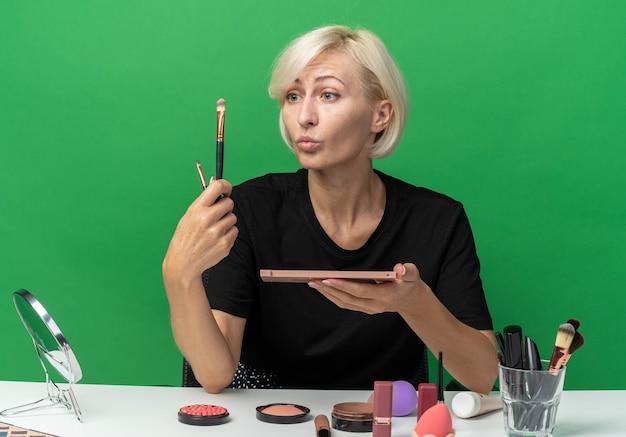 Beeindrucktes junges schönes mädchen sitzt am tisch mit make-up-tools, die lidschatten mit make-up-pinsel auf grüner wand auftragen