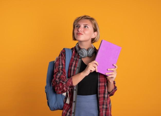Beeindrucktes junges slawisches studentenmädchen mit kopfhörern, das rucksack trägt, hält buch und notizbuch auf der seite