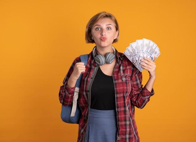 Beeindrucktes junges slawisches studentenmädchen mit kopfhörern, das rucksack trägt, hält geld